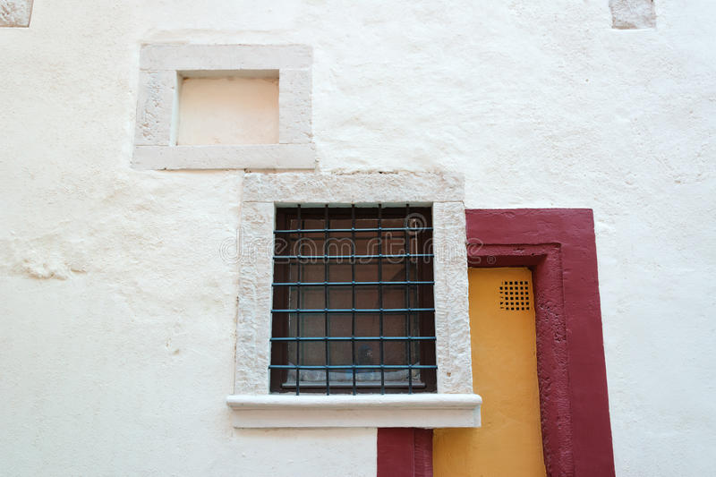 Art deco style wall with square windows. And red door frame stock photos