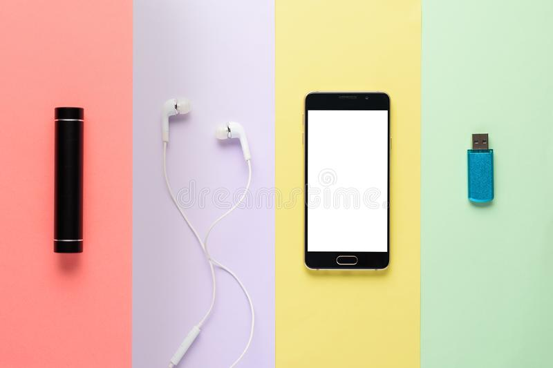 Art design concept gadgets. smartphone, power Bank, headphones, flash drive on a multi-colored striped background stock photos