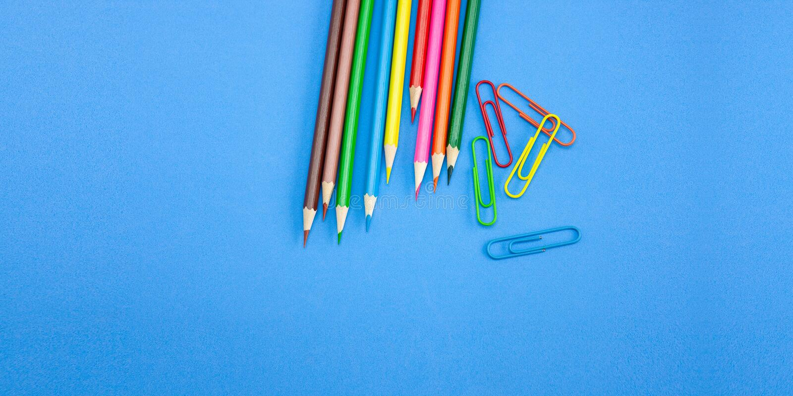 Art and drawing concepts, Colored crayon pencils and clips on blue background. Art and drawing concepts, Colored crayon pencils and clips at top corner on blue royalty free stock image