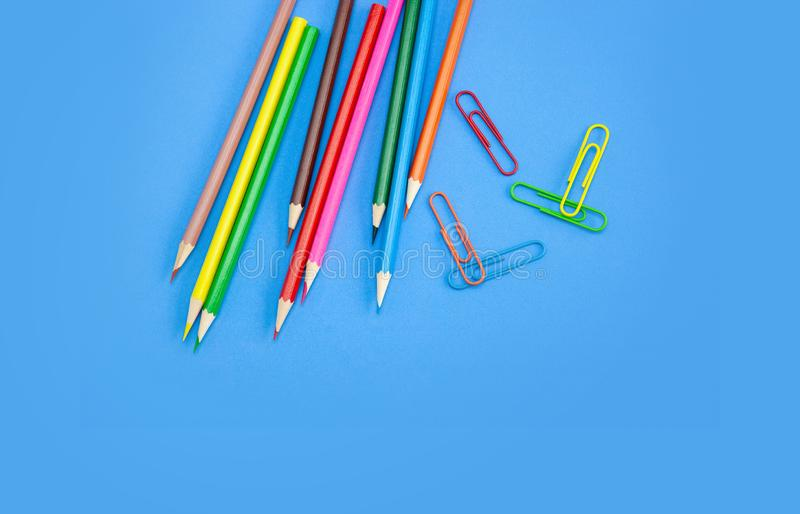 Art and drawing concepts, Colored crayon pencils and clips on blue background. Art and drawing concepts, Colored crayon pencils and clips at top corner on blue royalty free stock photos
