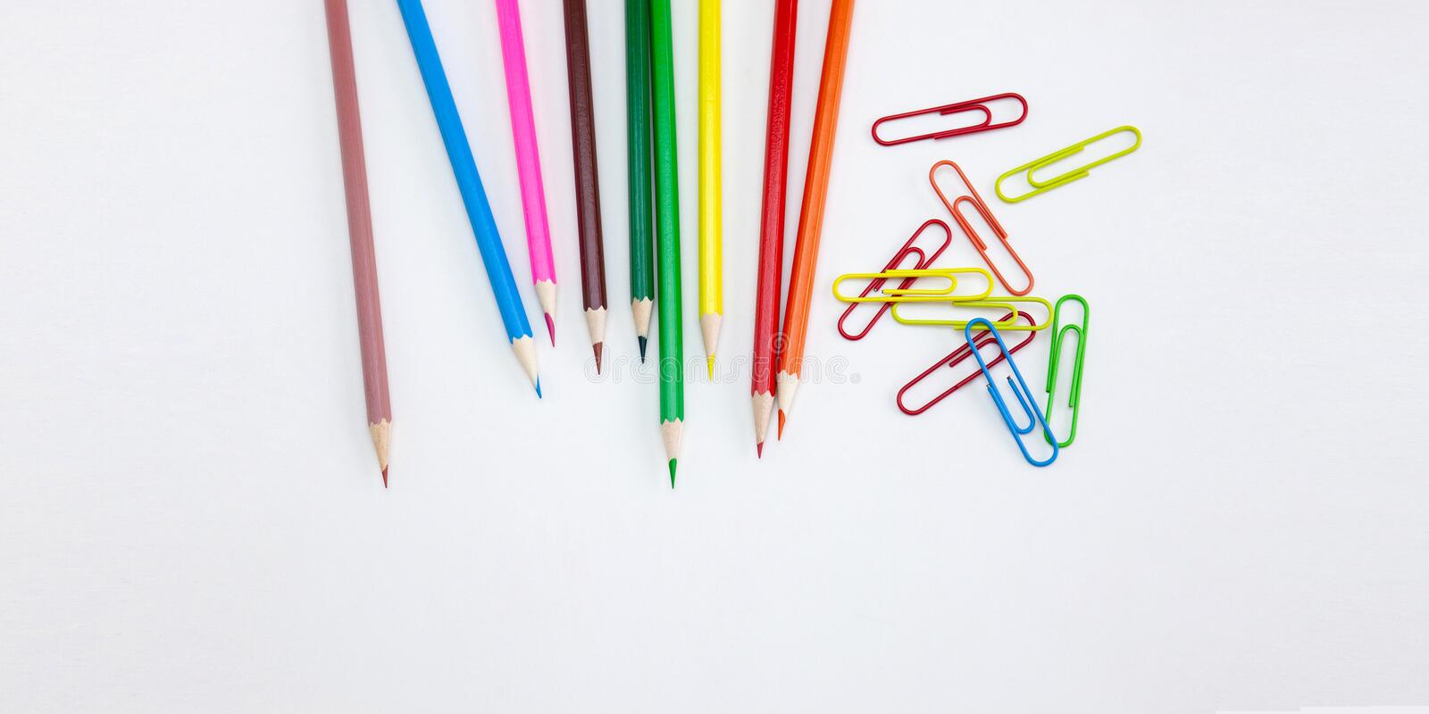 Art and drawing concepts, Colored crayon pencils and clips on white background. Art and drawing concepts, Colored crayon pencils and clips at top corner on white stock photo
