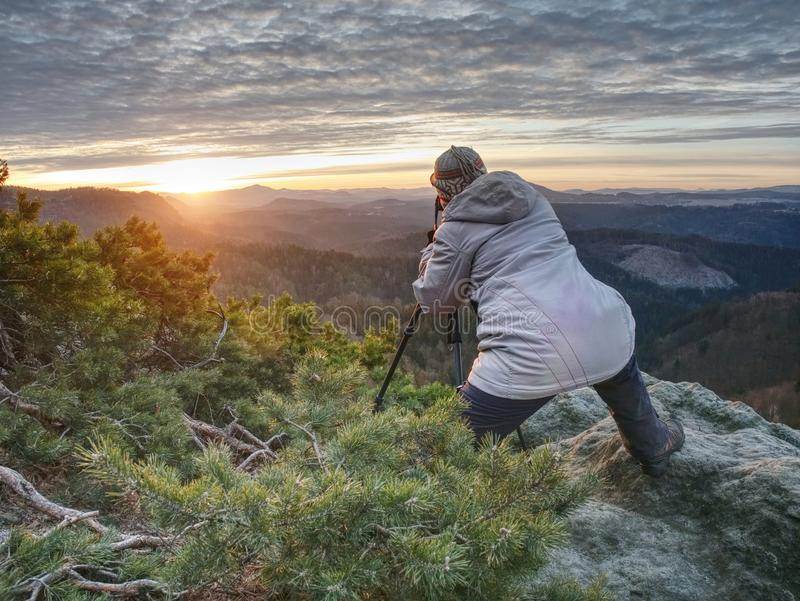 Art enthusiast with tripod on cliff. Peak with woman taking photos stock photo