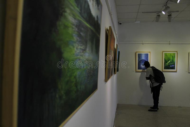 An art exhibition. Man viewing an art during Nepal-Bangaldesh friendship art exhibition at Kathmandu, Nepal on July 31, 2019 stock photos