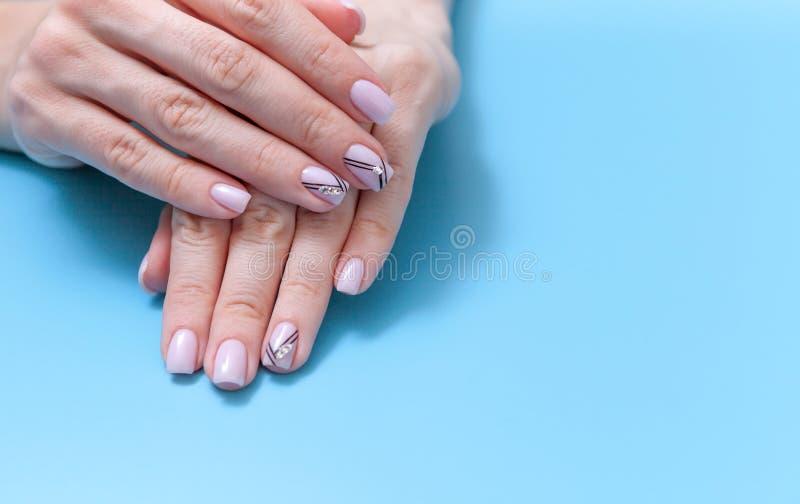 Art féminin à la mode, belle manucure unique d'ongle sur un fond bleu photos libres de droits