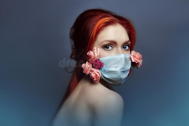Art fashion redhead woman with medical respirator on her face, rose flowers grow from under mask, clean air lack of oxygen stock photos
