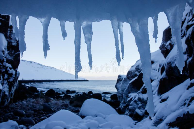Art frame of white snow cold icicles on top foreground and stones beach of north arctic ocean with snowy cliff and mountain on the royalty free stock images