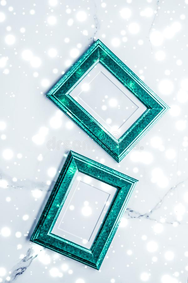 Emerald green photo frame and glowing glitter snow on marble flatlay background for Christmas and winter holidays. Art gallery, printable poster and online shop stock photos