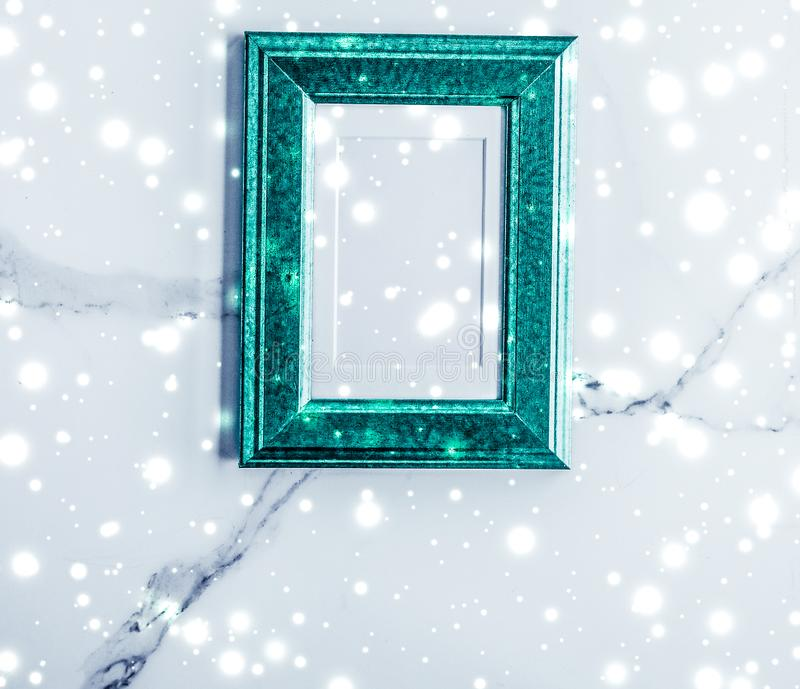 Emerald green photo frame and glowing glitter snow on marble flatlay background for Christmas and winter holidays. Art gallery, printable poster and online shop royalty free stock photo