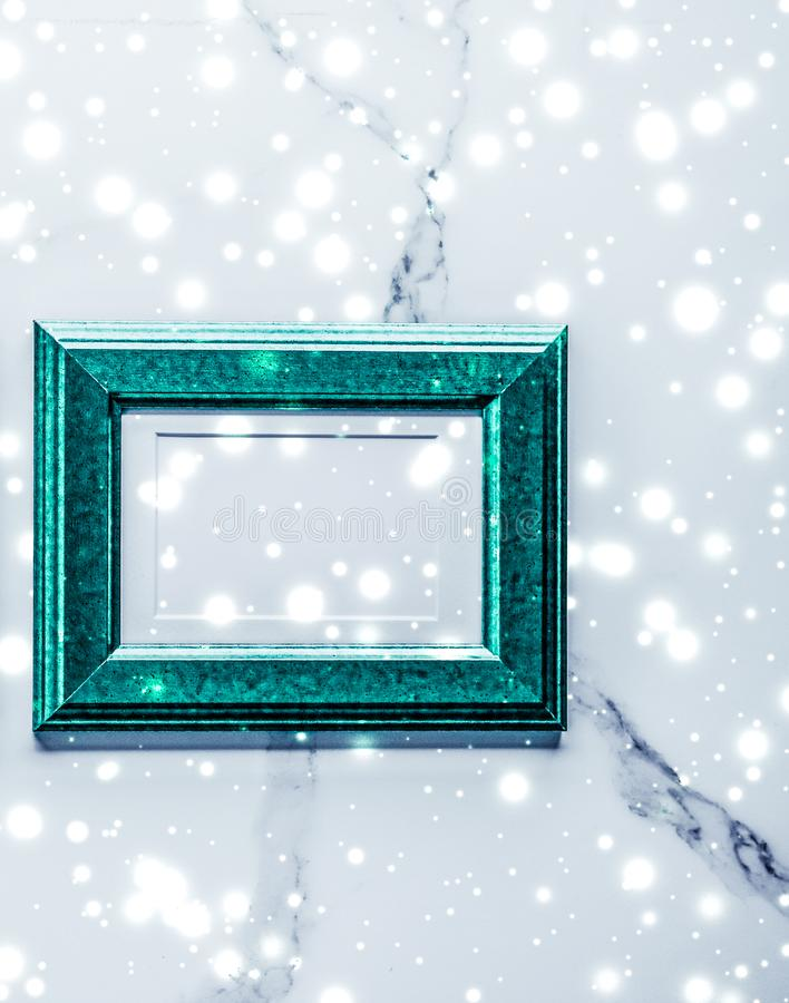 Emerald green photo frame and glowing glitter snow on marble flatlay background for Christmas and winter holidays. Art gallery, printable poster and online shop royalty free stock photography