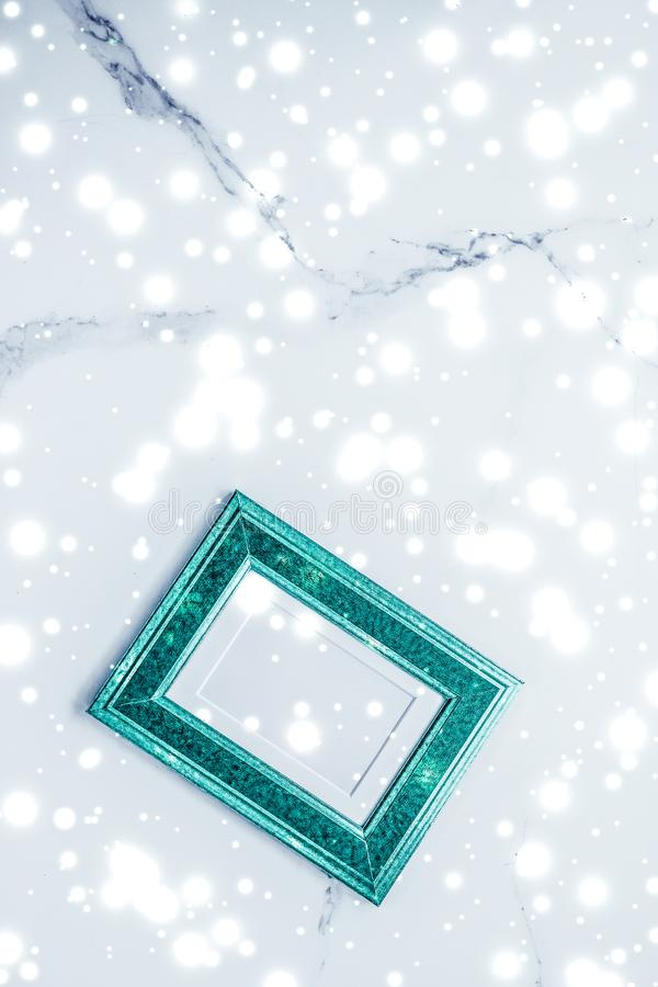 Emerald green photo frame and glowing glitter snow on marble flatlay background for Christmas and winter holidays. Art gallery, printable poster and online shop royalty free stock images
