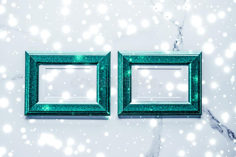 Emerald green photo frame and glowing glitter snow on marble flatlay background for Christmas and winter holidays. Art gallery, printable poster and online shop stock photo