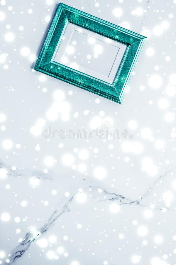 Emerald green photo frame and glowing glitter snow on marble flatlay background for Christmas and winter holidays. Art gallery, printable poster and online shop stock photography