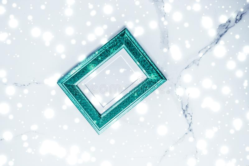 Emerald green photo frame and glowing glitter snow on marble flatlay background for Christmas and winter holidays. Art gallery, printable poster and online shop royalty free stock image