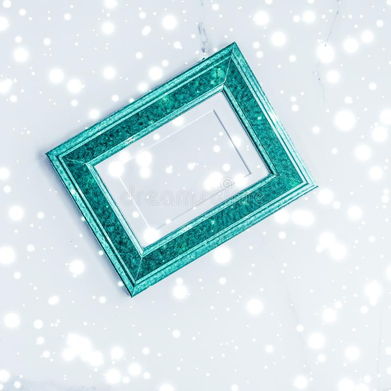 Emerald green photo frame and glowing glitter snow on marble flatlay background for Christmas and winter holidays. Art gallery, printable poster and online shop stock image