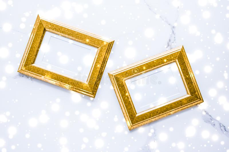 Golden photo frame and glowing glitter snow on marble flatlay background for Christmas and winter holidays. Art gallery, printable poster and online shop mockup stock image