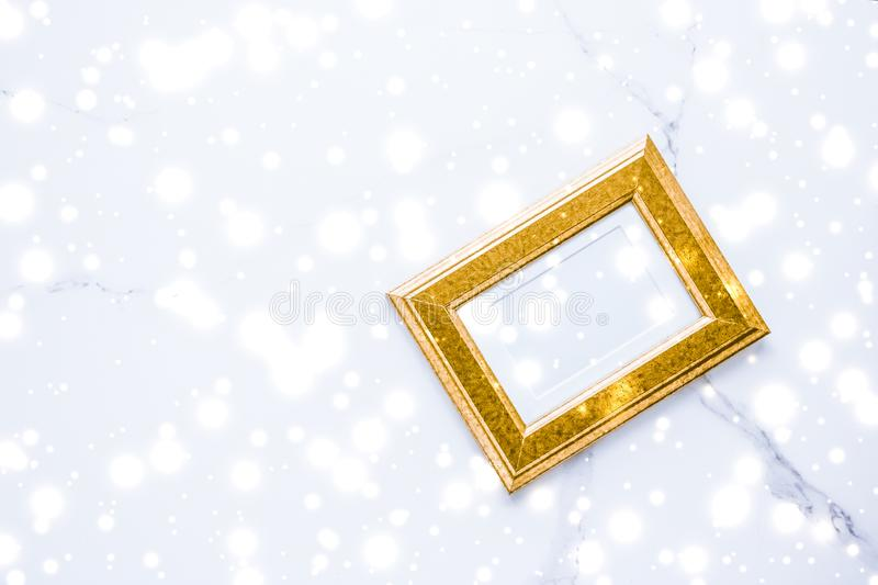 Golden photo frame and glowing glitter snow on marble flatlay background for Christmas and winter holidays. Art gallery, printable poster and online shop mockup royalty free stock photos
