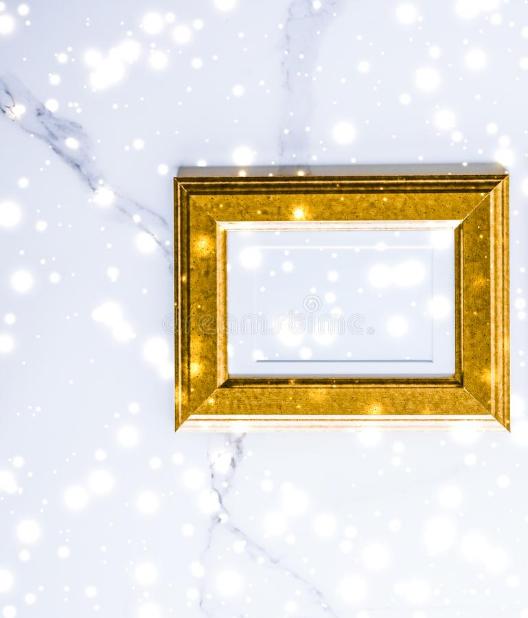 Golden photo frame and glowing glitter snow on marble flatlay background for Christmas and winter holidays. Art gallery, printable poster and online shop mockup royalty free stock images