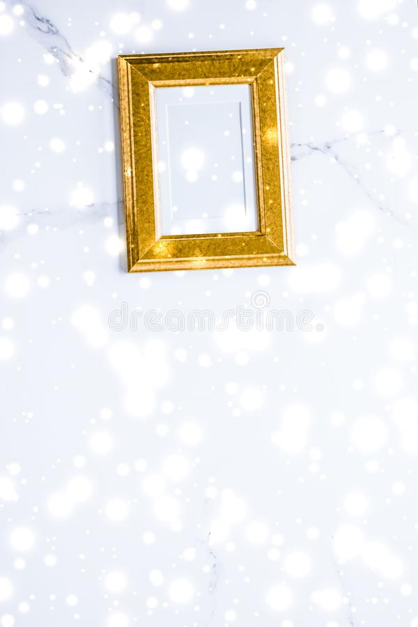 Golden photo frame and glowing glitter snow on marble flatlay background for Christmas and winter holidays. Art gallery, printable poster and online shop mockup stock images