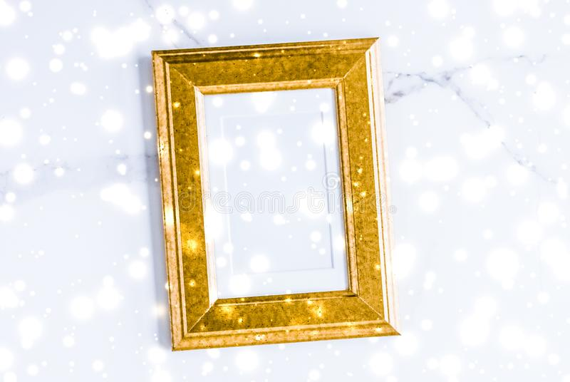 Golden photo frame and glowing glitter snow on marble flatlay background for Christmas and winter holidays. Art gallery, printable poster and online shop mockup stock photo