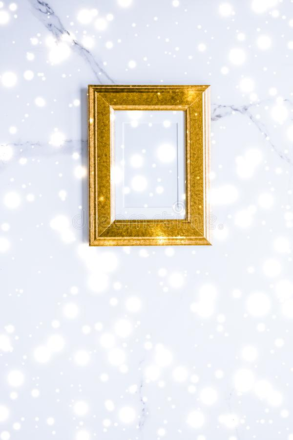 Golden photo frame and glowing glitter snow on marble flatlay background for Christmas and winter holidays. Art gallery, printable poster and online shop mockup royalty free stock image