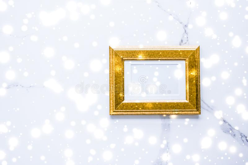Golden photo frame and glowing glitter snow on marble flatlay background for Christmas and winter holidays. Art gallery, printable poster and online shop mockup royalty free stock photography