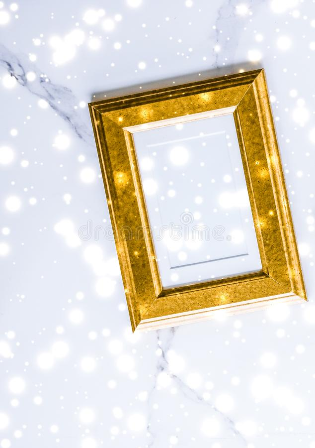 Golden photo frame and glowing glitter snow on marble flatlay background for Christmas and winter holidays. Art gallery, printable poster and online shop mockup stock photos