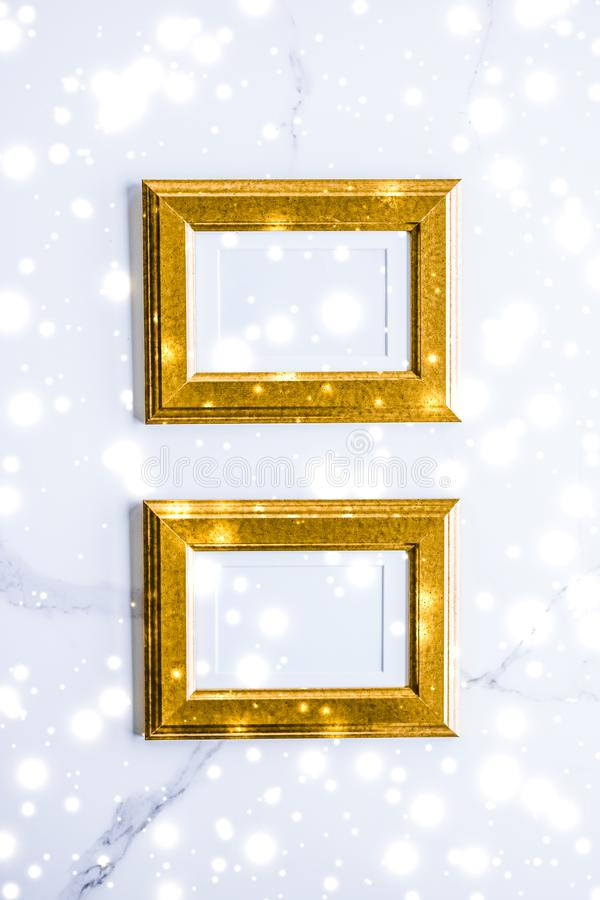 Golden photo frame and glowing glitter snow on marble flatlay background for Christmas and winter holidays. Art gallery, printable poster and online shop mockup stock photography
