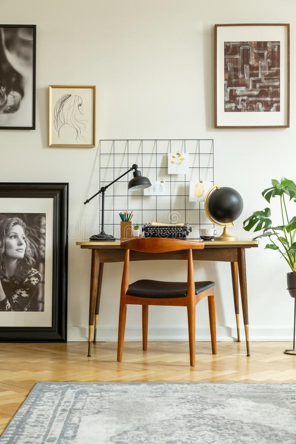 Art gallery in a retro home office interior with a desk and chair. Real photo. Concept stock image
