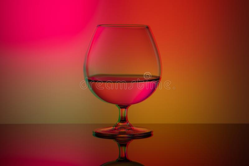 Art glitch effect, glass glass with water on a bright multi-colored background, minimalism. Art glitch effect, glass glass with water on bright multi-colored stock images