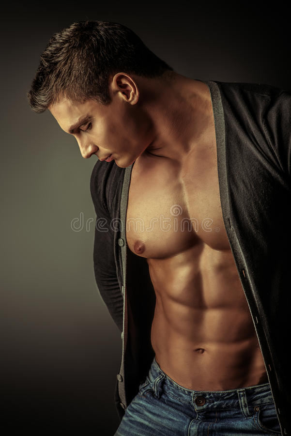 Art handsome. Portrait of a muscular young man posing over dark background