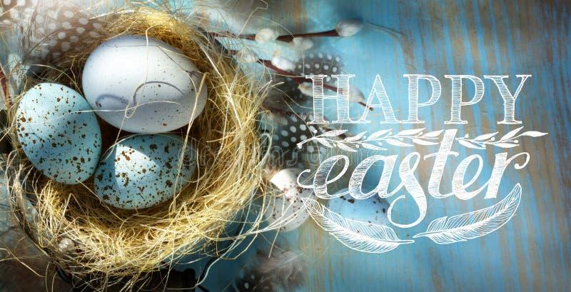 Art Happy Easter; Påskägg i korg på den blåa tabellbackgrouen arkivfoton