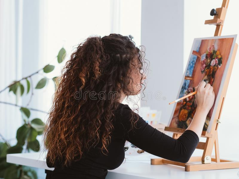 Art hobby talented lady still life painting home. Art hobby. Back view of talented lady with beautiful curly hair working on still life painting at home studio royalty free stock photo