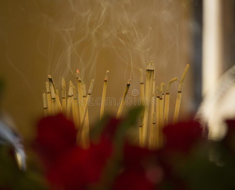 Yellow candle on the pot with sand.Art of incense sticks in joss-stick pot at the temple. royalty free stock image