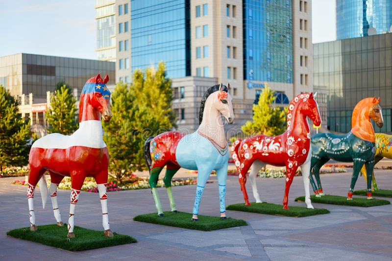ASTANA, KAZAKHSTAN - JULY 25, 2017: Art installation with figures of horses painted in different ethnic ornament in Astana. Art installation with figures of royalty free stock images