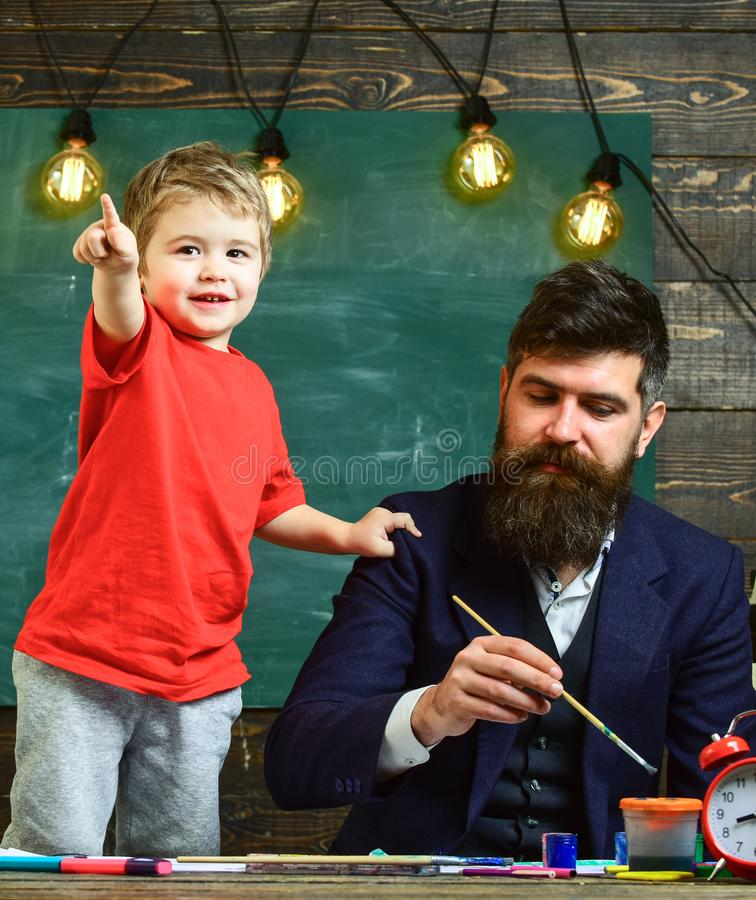 Art lesson concept. Talented artist spend time with son. Child cheerful and teacher painting, drawing. Teacher with stock photography
