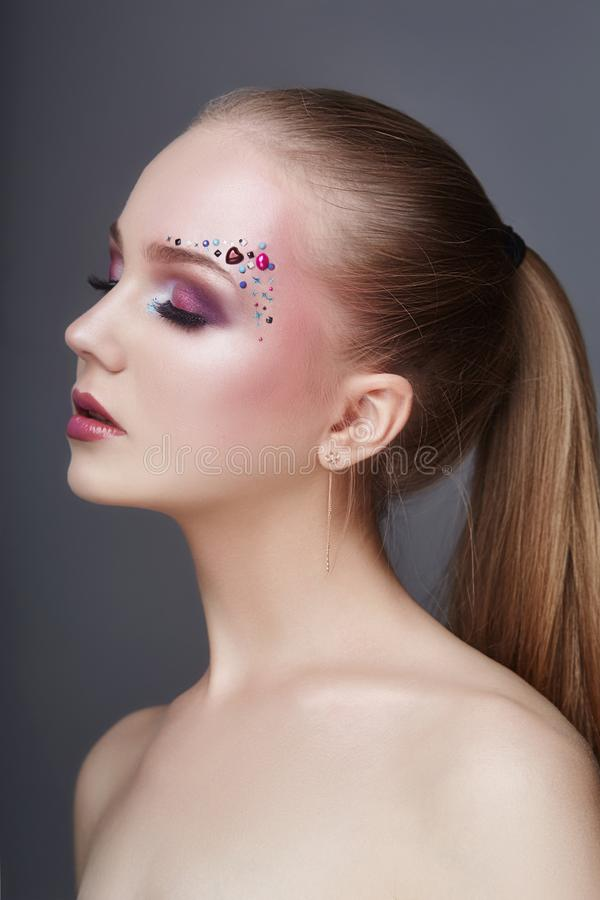 Art makeup over the eyebrows of women many rhinestones of different shapes, beautiful face smooth skin care. Beauty makeup. Art makeup over the eyebrows of woman royalty free stock photos