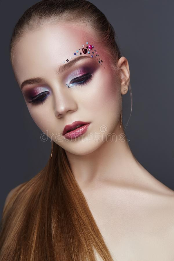 Art makeup over the eyebrows of women many rhinestones of different shapes, beautiful face smooth skin care. Beauty makeup. Art makeup over the eyebrows of woman royalty free stock image