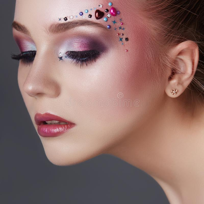 Art makeup over the eyebrows of women many rhinestones of different shapes, beautiful face smooth skin care. Beauty makeup. Art makeup over the eyebrows of woman royalty free stock images