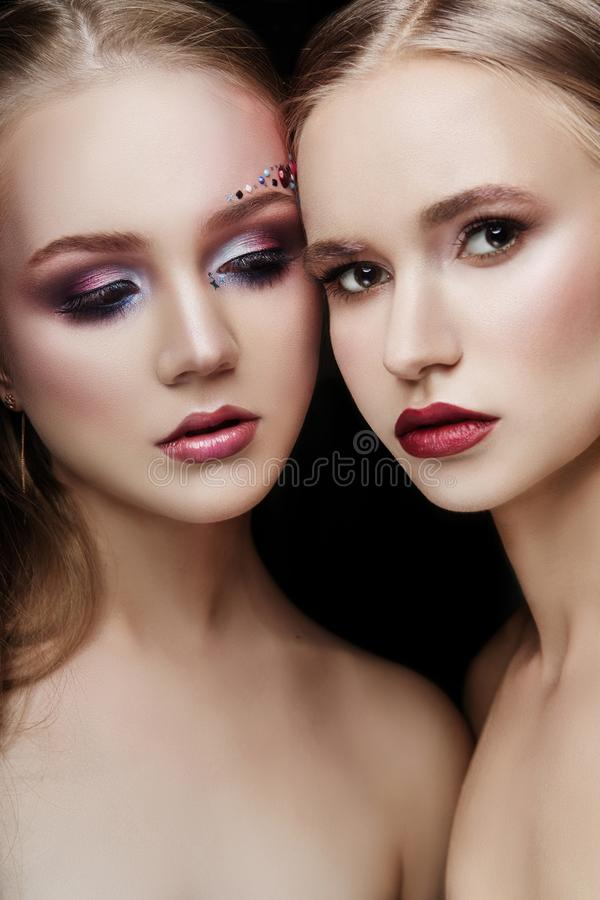 Art makeup two girls hugging, lots of rhinestones of different shapes, beautiful face smooth skin care. Beauty makeup on the face. Of two women close-up royalty free stock photography