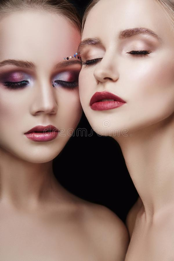Art makeup two girls hugging, lots of rhinestones of different shapes, beautiful face smooth skin care. Beauty makeup on the face. Of two women close-up stock images