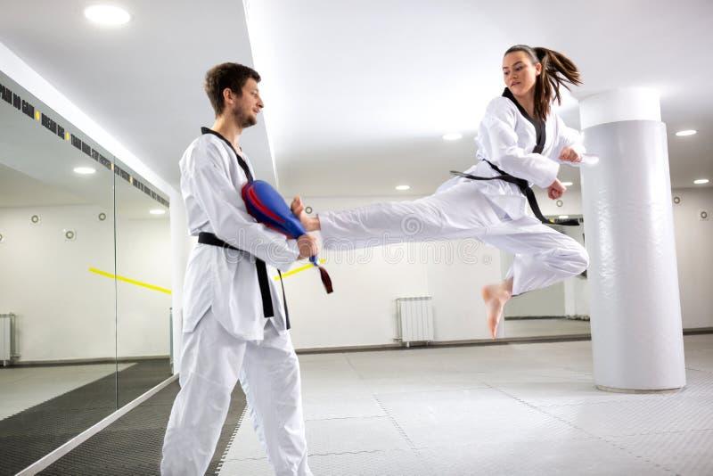 Art martial de formation de jeune fille du Taekwondo exécutant un coup-de-pied d'une position sautante photos libres de droits