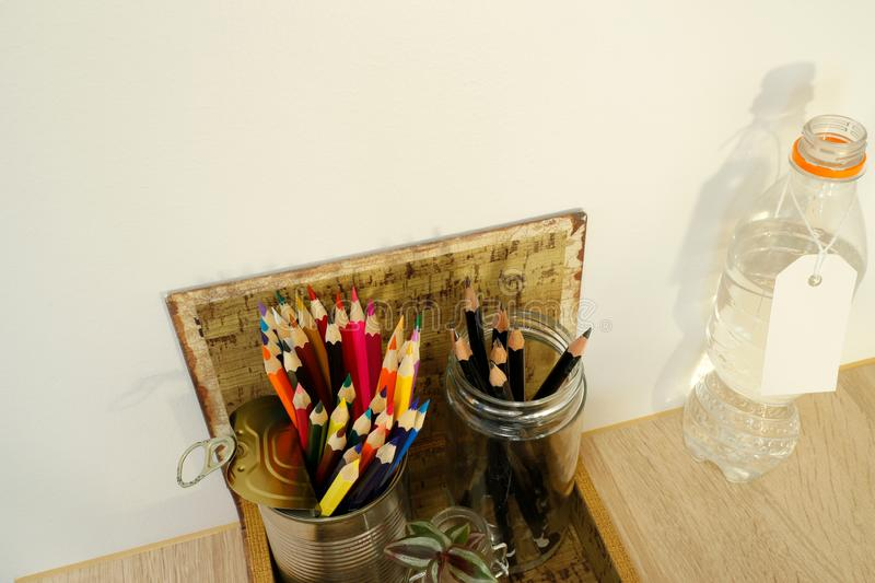 Household waste reused as pencil holders. Glass jar and metal tin can. Organized space royalty free stock image