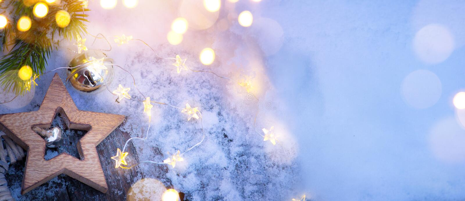 Merry Christmas blue snowy background and fir tree branches with holidays lights royalty free stock photography