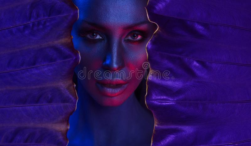 Art neon Portrait of Beautiful Young Woman with glamorous mystical makeup. Art neon Portrait of Beautiful Young Woman with make-up. Woman`s face surrounded by stock image