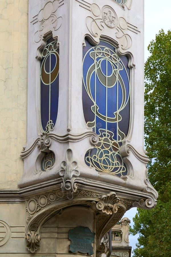 Art Nouveau-het erkerraamdetail van Fenoglio Lafleur van de de bouwvilla met bloemendecoratie in Turijn stock foto