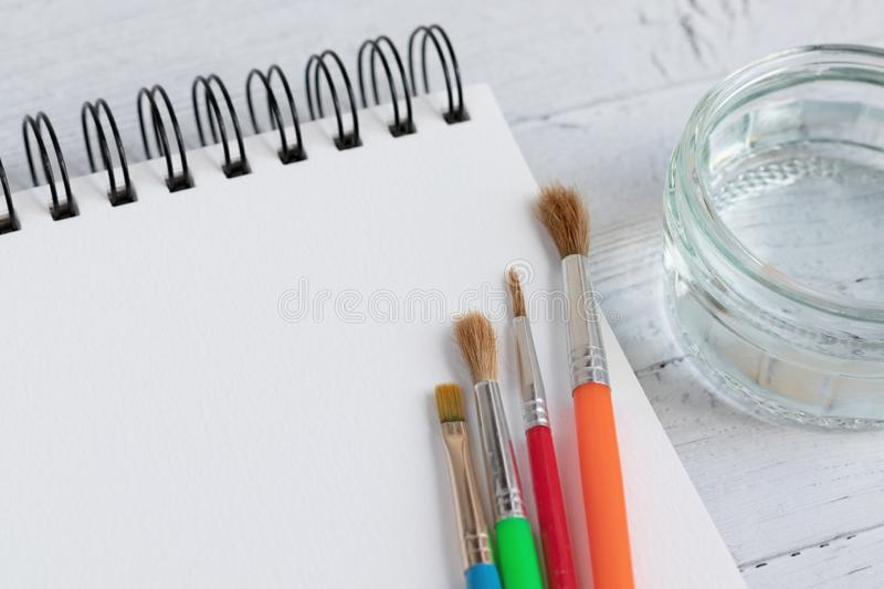 Art pad, paint brushes and glass of water on a wooden surface. Artist desk with a very shallow depth of field stock image