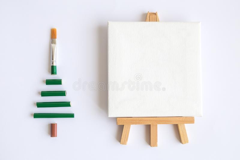 Art paint brush in form of christmas tree and canvas on easel abstract. Flat lay of christmas tree made of paint brush and blank art canvas on easel minimal stock images