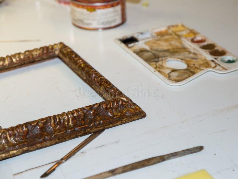 Art Palette, spazzole e struttura dorata di legno dentro il negozio di ripristino fotografie stock libere da diritti