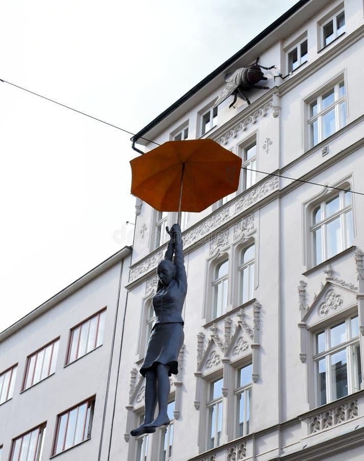 Art Performance med kvinnan som hänger vid paraplyet i Prague arkivbild