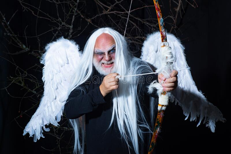 Art photo of a Angelic man. Senior man posing with angel wings. Evil vampire man. Man wizard with fantastic make up on. Demon face. Druid on black background royalty free stock photos